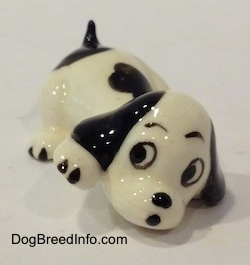 The front right side of a figurine of a white with black puppy figurine that is in a lying pose. The figurine has black circles for eyes and a nose.