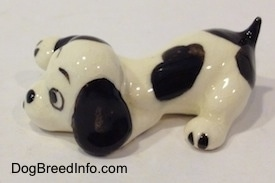 The left side of a white with black puppy figurine that is in a lying pose. The figurine has a short black tail.