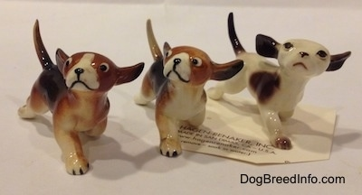 The front right side of three figurines of running dogs in different color variations. The figurines are looking up and to the left.