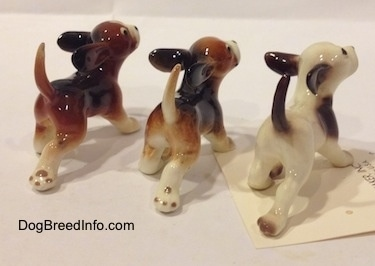 The back right side of three running dog figurines in different color variations. The figurines tails are arched up in the air.