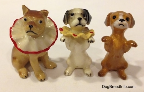 Three circus dog figurines and two of them are in a begging pose.
