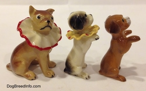 The right side of three circus dog figurines. Two of the figurines are wearing neck ruffles.