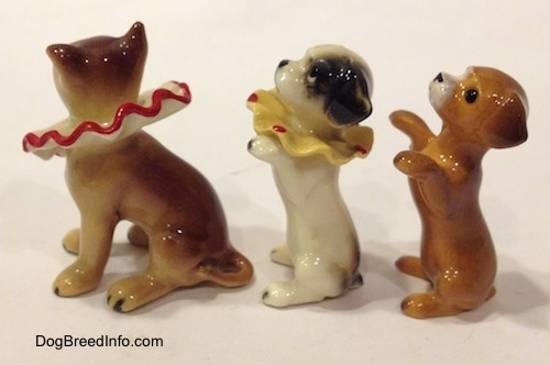 The left side of three figurines of circus dogs. The right most figurines have short tails and the forward most figurine has a medium length tail.