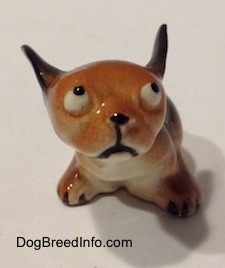A running puppy miniature figurine. The figurines ear are up as they are flying back.