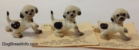 The right side of three white with brown Hound dog figurines. All the figurines have black circles for eyes.