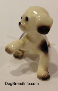 The front of a brown spotted Hound dog figurine with a paw in the air. The figurine has brown at the bottom of its ears.