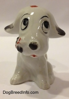A white with black bone china mixed breed dog figurine that is in a sitting pose.