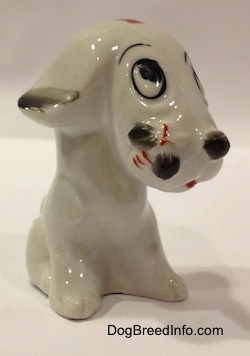 The front right side of a white with black sitting mixed breed dog figurine. The figurine has a bumblebee on its snout.