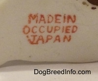 Close up - A stamp on the underside of a mixed breed dog figurine that reads 'Made in Occupied Japan'.