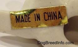 Close up - The underside of a bone chine puppy lying down figurine and there is a gold sticker that reads 'Made In China'.