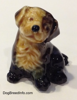 A ceramic black, brown and tan puppy figurine. The figurine does not have eyes painted on. It looks like the figurine has a smile on.