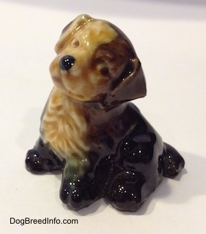 The left side of a ceramic black, brown and tan puppy figurine. It is looking to the left and the head of the figurine is tilted to the right. It has a black nose and a cute face.