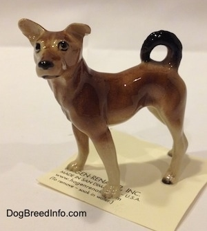 The left side of a figurine of a mixed breed dog.