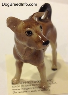 A figurine of a mixed breed dog. The figurine is looking to the right.