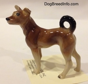 The left side of a mixed breed dog figurine. The figurines tail is curled up onto its back.