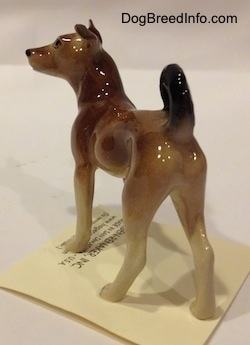 The back left side of a mixed breed dog figurine. The figurine has long legs.