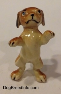A figurine of a dog standing on its hind legs in a begging pose.