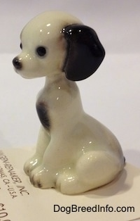 The left side of a figurine of a white with black sitting puppy. The puppy has balck circles for eyes.