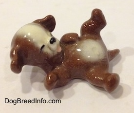 A figurine of a brown with white dog that is laying on its back.
