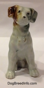 A bone china brown, white and black mixed breed dog in a sitting pose figurine.