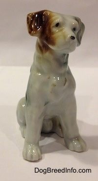 The front right side of a figurine of a bone china brown, white and black mixed breed dog in a sitting pose. The figurine has black circles for eyes.