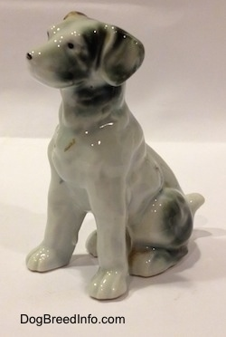 The front left side of a bone china brown, white and black figurine of a mixed breed dog in a sitting pose. The figurine has long limbs.