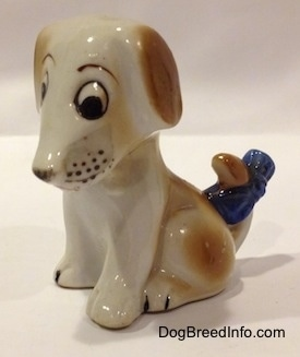 A brown and white mixed breed puppy figurine in a sitting pose.