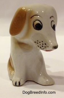 The front right side of a brown and white mixed breed puppy figurine in a sitting pose. The figurine has cartoon-y features.