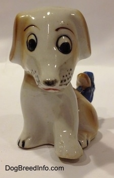 A figurine of a brown and white mixed breed puppy figurine. The figurines eyes are slightly off.