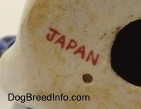 Close up - On the underside of a figurine of a mixed breed dog is a red 'JAPAN' stamp.