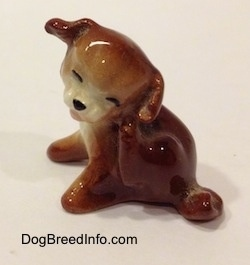 A figurine of a brown with white puppy scratching its neck.