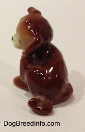 The back of a brown and white figurine of a puppy scratching its neck. The figurine has a short curled taill.