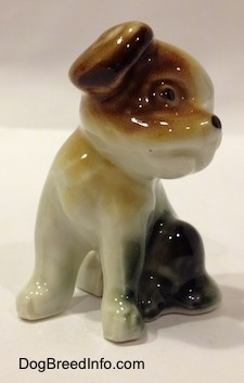 The front left side of a figurine of a brown, black and white dog that is sitting. The figurine has detailed black circles for eyes.