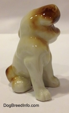 The front right side of a brown, black and white dog sitting figurine. The figurines ears are attached to the