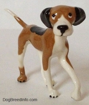 The front right side of a tri-color Papa Dog figurine. The figurine has long and skinny legs.