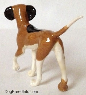 The back left side of a Papa Dog figurine that is tri-color. The figurine has black ears.