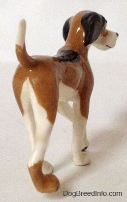 The back right side of a figurine of a Papa Dog. The figurine has a long body.