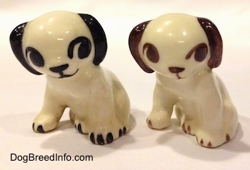 Two figurines of a dog in a sitting position. The figurines are different color variations.