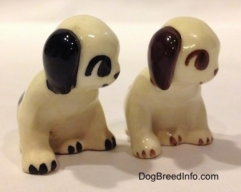 Two dog figurines that are in a sitting position. They have big circles for eyes.