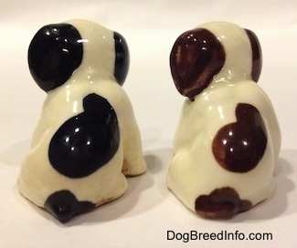The back of two dog figurines in a sitting position that are different color variations. The figurines have ears that are a solid color.