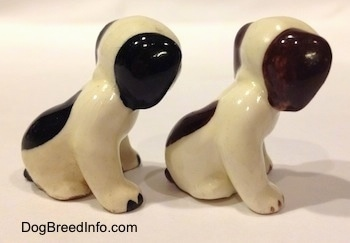 The right side of two dog figurines that are in a sitting positions and are different color variations. The figurines have color tipped nails.