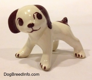 A white with brown dog standing figurine. The figurine has colored parts.