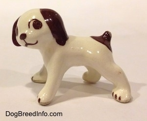 The left side of a white with brown dog standing figurine. The figurine has a short brown tail with a brown spot around it.