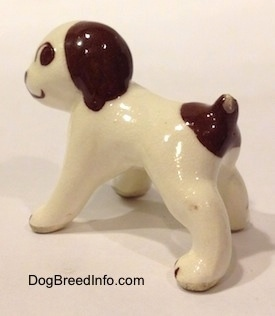 The back left side of a white with brown dog standing figurine. The figurine has large brown eyes.