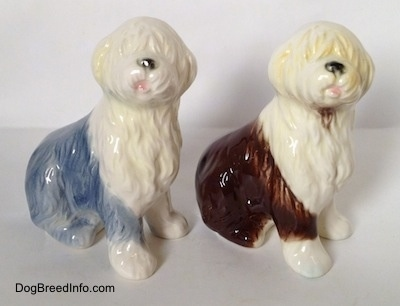 Two porcelain Old English Sheepdog figurines that are in a sitting positions. The figurines both have there mouths open.
