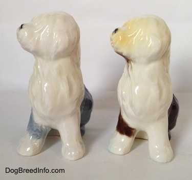 Two color variations of a porcelain Old English Sheepdog figurine that are in a seated position.