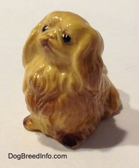 The front left side of a tan Pekingese figurine. The figurine has detailed black circles for eyes.