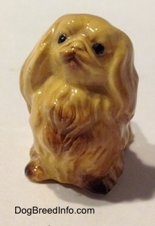 The front left side of a tan figurine of a Pekingese. The figurine is looking up.