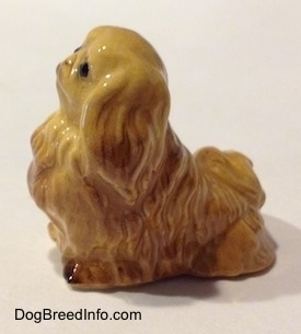 The left side of a tan Pekingese figurine.