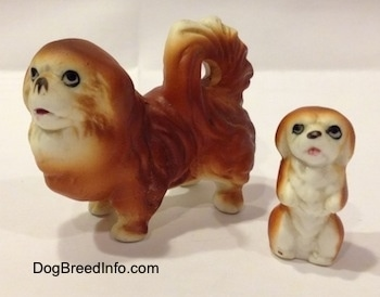 A brown with white Pekingese figurine and next to it is a brown with white Pekingese puppy figurine in a begging pose.